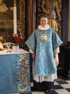 Pastor Hanne Beierholm Christensen med messehagel broderet af HKH Dronning Magrethe i 2019, set forfra. Anvendt broderiteknik er 'petitpoint'.