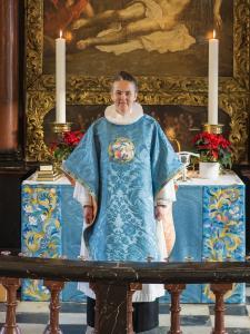 Pastor Hanne Beierholm Christensen med messehagel broderet af HKH Dronning Magrethe, set forfra. Anvendt broderiteknik er 'petitpoint'.